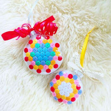 Set of two Christmas ornaments covered with bright colored buttons and red and polka dot ribbon bows at top