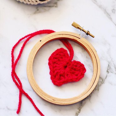 Red crochet heart ornament inside embroidery hoop