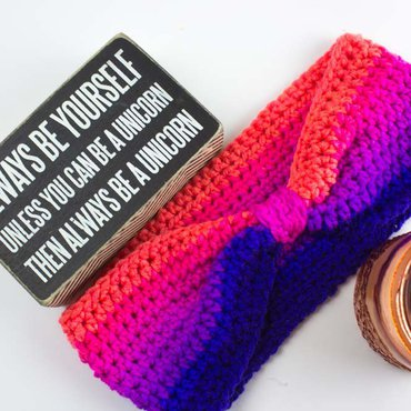 Crochet ombre headband with candle and unicorn sign nearby
