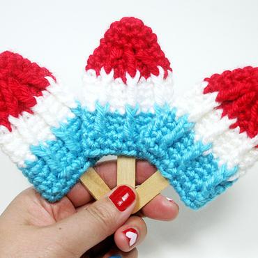 Hand holding three crochet rocket popsicles