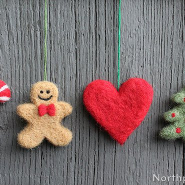 Set of 4 felted cookie shaped ornaments: candy cane, gingerbread man, heart, and Christmas tree on a wood background