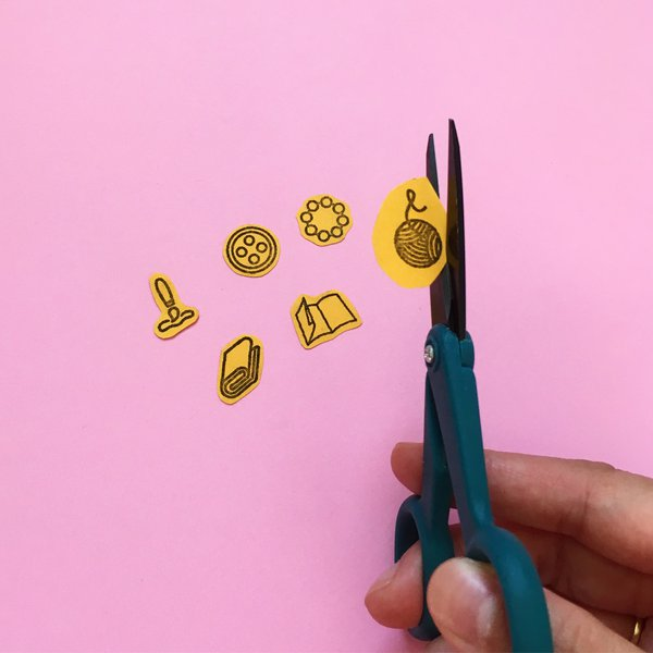 Closeup of hand fussy cutting icons on cardstock paper with scissors