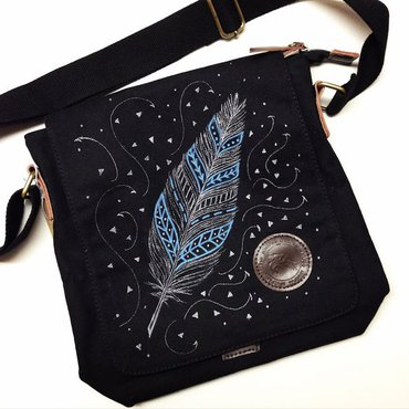 Hand painted blue and white feather design on black purse with white swirls and triangles around feather design
