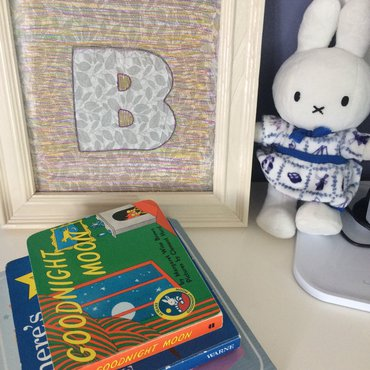 Knockout monogram frame and stack of children's books and bunny toy