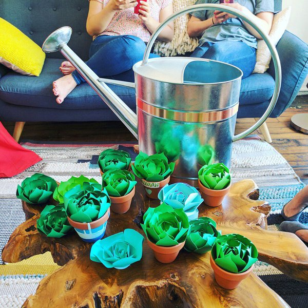 A selection of green paper succulents and watering can on wood center table; two people sitting on couch behind the table