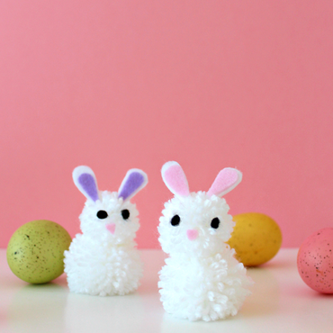 Set of pom pom bunnies with Easter eggs against pink background